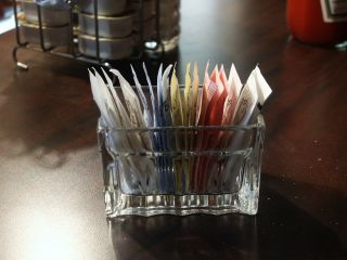Packets of sweeteners sit on a table.