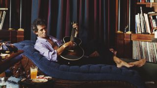 English guitarist Keith Richards of the Rolling Stones playing a guitar on a chaise longue in his library, circa 1995