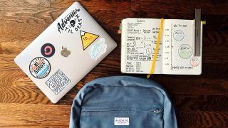 PC, arbeidsbok og skolesekk på en bord