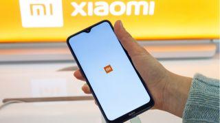 Xiaomi smartphone held in front of company logo