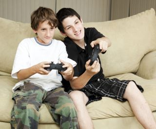 Two teenage boys play a game.