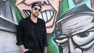 A photo of Caleb Shomo stood next to a wall with graffiti on it