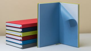 Stack of hardcover notebooks with brightly coloured covers, with one open
