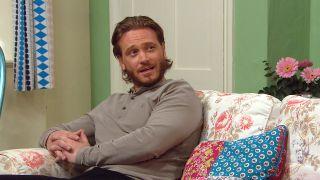 David Metcalfe sits on Victoria's sofa in Emmerdale.