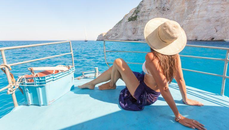 Woman on boat in front of famous shipwreck beach. Zakynthos, Greek Islands, Greece