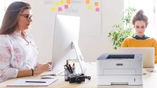 best laser printer: Two women working at a desk containing a Xerox laser printer