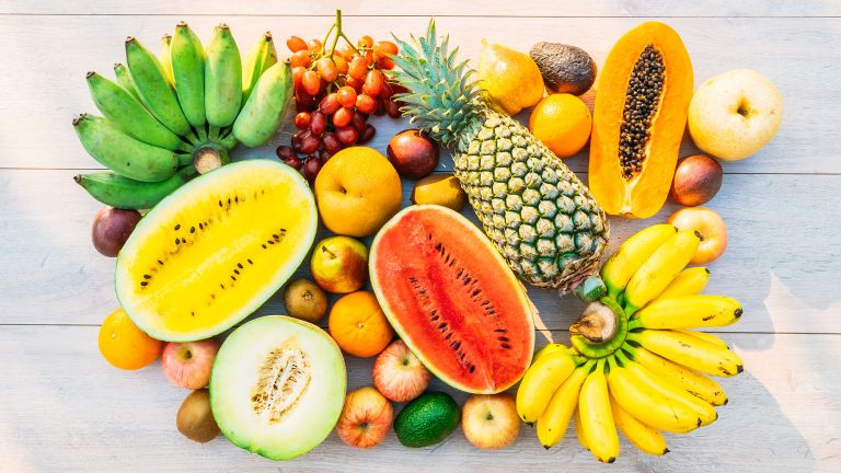 Selection of fruits, including bananas, pineapple, watermelon and grapes, illustrating the question 'is fruit healthy?'