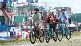 How to buy an electric bike: three riders on e-bikes cycle on a bike path