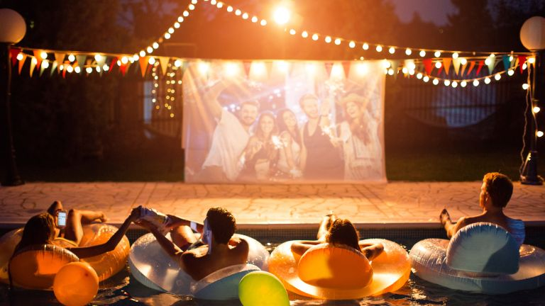 the best outdoor projector: friends enjoying outdoor projector in garden