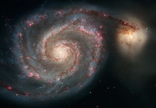n this Hubble image, the Whirlpool Galaxy (M51a) and a companion (M51b) are merging. The two galaxies are similar in mass to the Milky Way and the Large Magellanic Cloud.