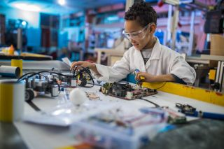 Smiling boy with safety glasses works on circuit board.