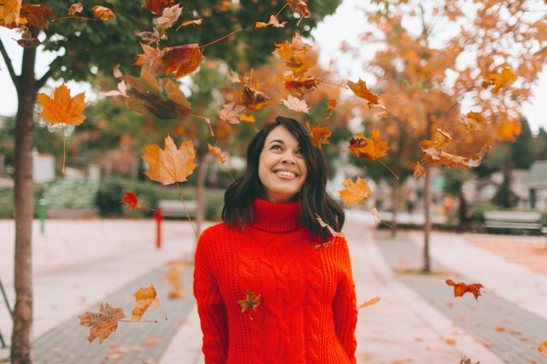 Smiling Woman Looking At Leaves While Standing On Footpath During Autumn, Autumn Equinox 2021