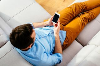 A person sitting on a couch holding a smartphone.