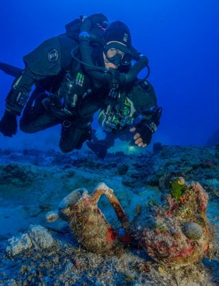 An archaeologist dives at the site of the Antikythera shipwreck.