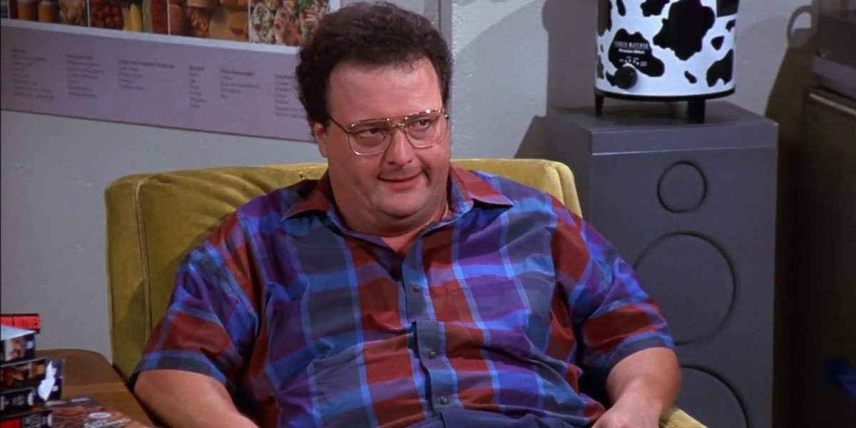Newman sitting in his chair and looking angry on Seinfeld.