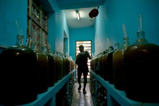 In this photo, taken on March 30, 2017, winemaker Orestes Esteves moves a jug of wine, at his house in Havana, Cuba.
