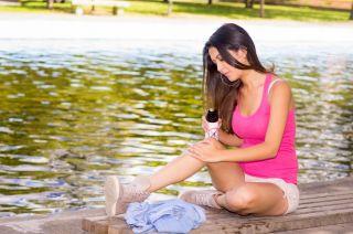A woman sprays bug spray onto her legs while sitting next to a lake,