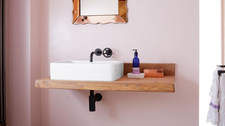 Basin against a pink wall with black bathroom taps