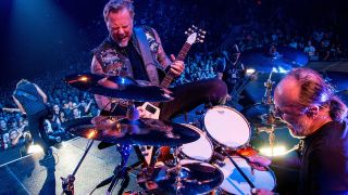 A photograph of James Hetfield and Lars Ulrich on stage - both are shouting