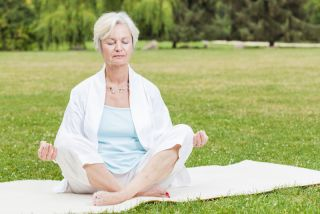 An older woman sits in a green field, meditating.