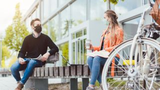 two college students sit outside on either end of a bench, both are wearing face masks and have laptops and books out