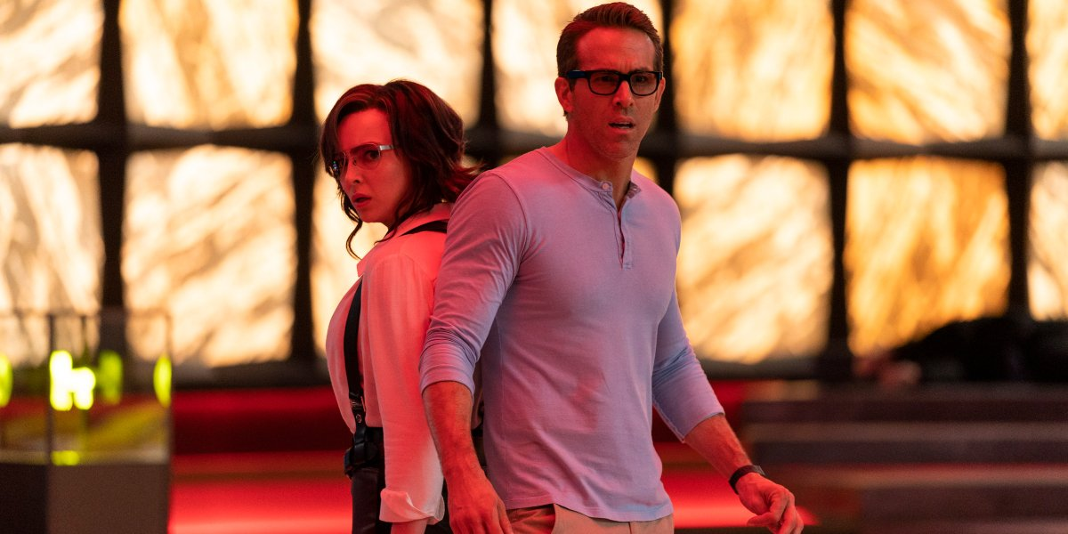 Jodie Comer and Ryan Reynolds standing back to back in the stash house in Free Guy.