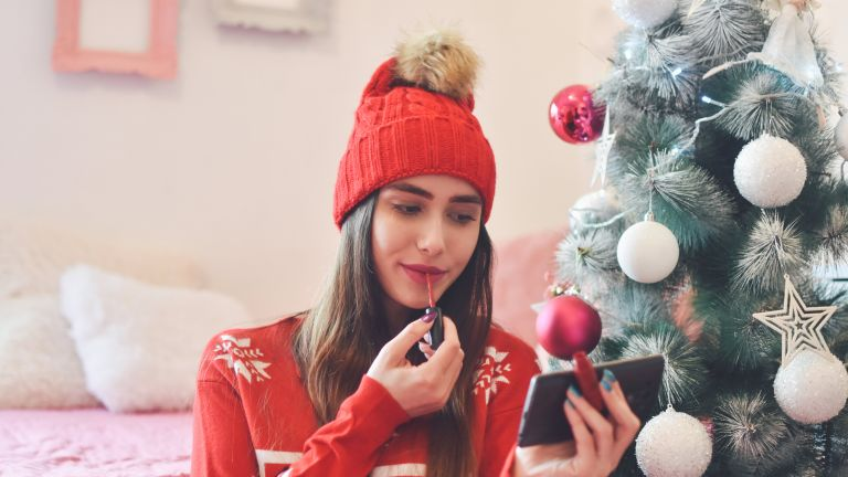 woman applying make-up in front of Christmas tree