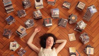 A woman lies on the floor listening to old CDs