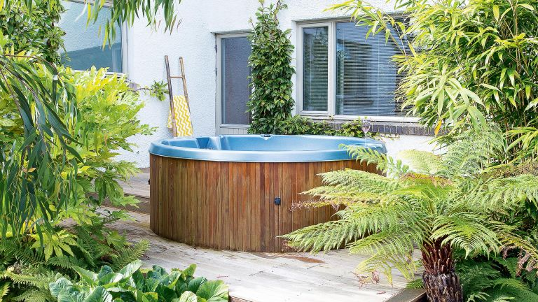 hot tub maintenance: hot tub on decking with surrounding plants
