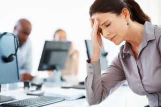 A woman looks stressed at work, while colleagues sit in the background.