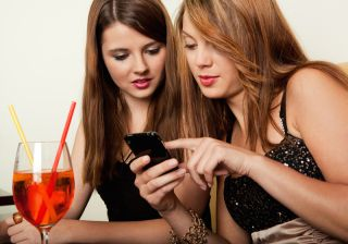 Two women have a drink and look at a smartphone