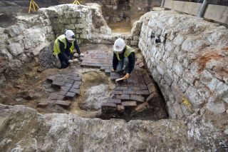 MOLA archaeologists excavate the top of the cesspit, which had been backfilled and covered over with several layers of brick flooring.