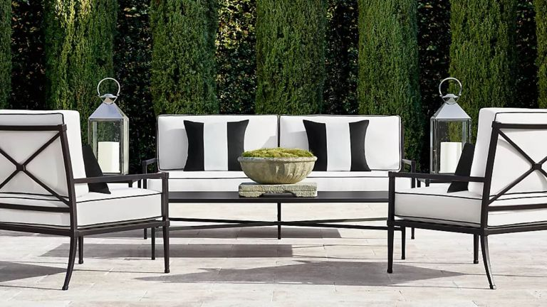 A black and white outdoor furniture set on a paved courtyard