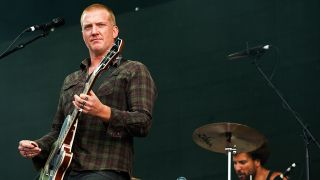a photo of josh homme on stage
