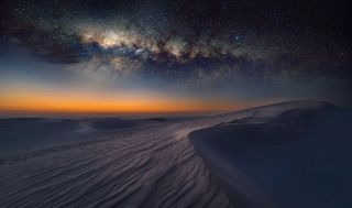 The milky way shines in the night sky over the Sahara Desert.