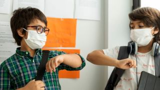 two boys in face masks bump elbows while standing near a wall in school