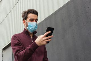 A man wearing a medical mask checks his phone.