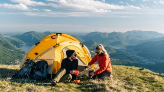 two campers outside a tent