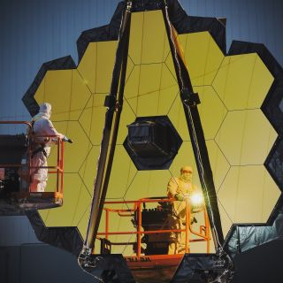 Large assembly of hexagonal gold mirrors with technicans inspecting