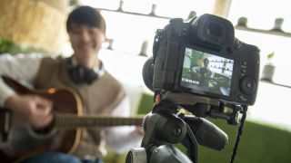View from behind the camera as a man records a guitar performance