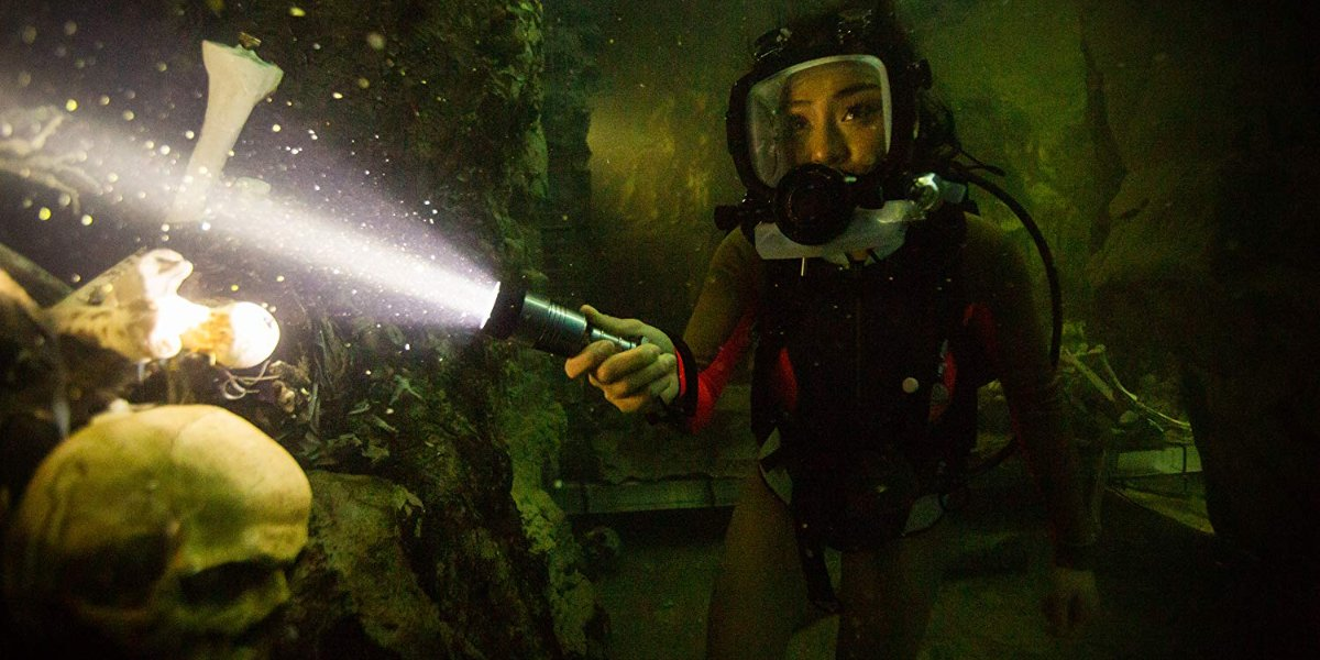 47 Meters Down: Uncaged a diver shining her light on some skeletal debris