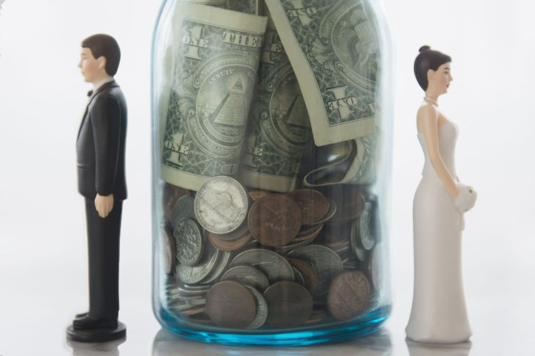 Bride and groom figures on either side of savings jar