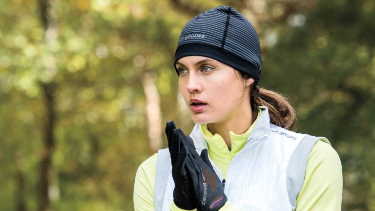best running gloves: woman wearing running hat and running gloves