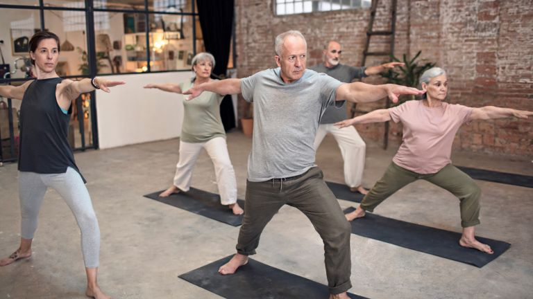 Group of seniors lunge forward in a yoga class