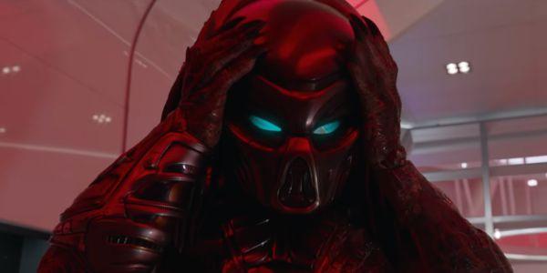 The Predator putting on his helmet