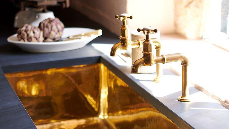 deVOL's shiny brass sink in a dark kitchen