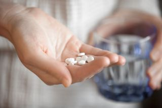 A person holds a handful of pills.