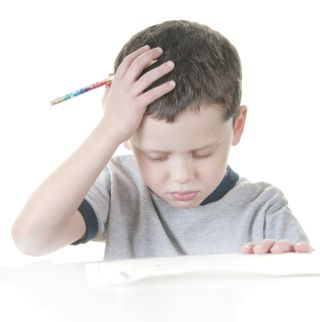 A little boy works on school work, with a look of frustration on his face.