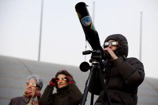 Skywatchers observe a partial solar eclipse