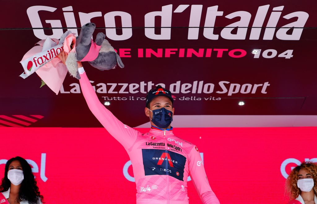 Team Ineos rider Italys Filippo Ganna wearing the overall leaders pink jersey celebrates on the podium after winning the first stage of the Giro dItalia 2021 cycling race a 86 km individual time trial on May 8 2021 in Turin Photo by Luca Bettini AFP Photo by LUCA BETTINIAFP via Getty Images